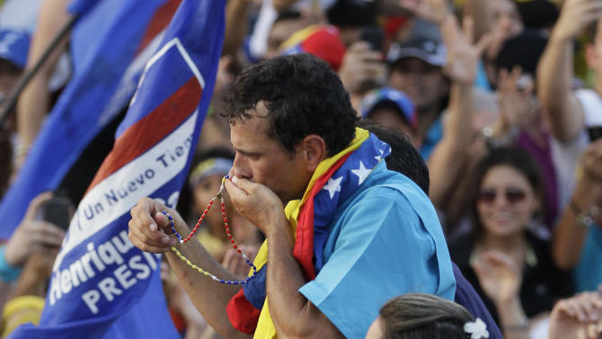 Opposition presidential candidate Henrique Capriles kisses a religious rosary during a campaign rally in Maracaibo, Venezuela, Wednesday, Oct. 3, 2012. Capriles will run against President Hugo Chavez in the presidential elections Oct. 7. (AP Photo/Ariana Cubillos)