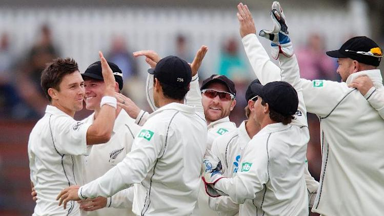 Trent Boult (L) of New Zealand celebrates with his team after winning their second Test match against West Indies, on day three, at the Basin Reserve in Wellington, on December 13, 2013