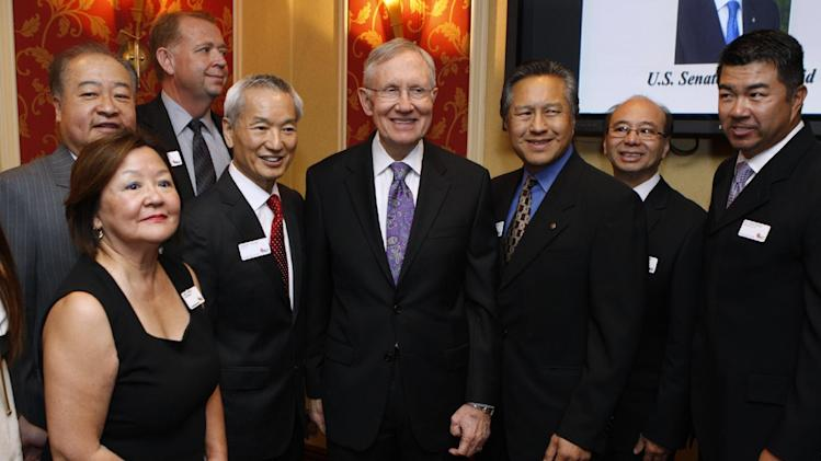 U.S. Sen. Harry Reid, D-Nev., center, takes photographs with members of the Asian Chamber of Commerce prior to taking the stage during their monthly lunch at the Gold Coast casino-hotel in Las Vegas. Reid, the Democratic Senate Majority Leader, apologized Friday for jokes he made about Asians during the luncheon. (AP Photo/Las Vegas Review-Journal, Erik Verduzco) LAS VEGAS SUN OUT