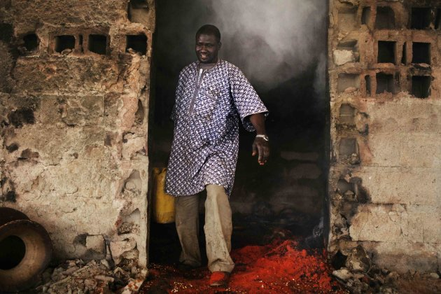 Shopkeeper Mohamed Toure leaves his destroyed shop after pouring water on a fire in the stop at the main market in Gao