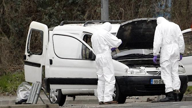 Police forensic officers examine a car in which four mortar rounds were found in Londonderry, Northern Ireland, Monday, March 4, 2013. Northern Ireland police say they seized a van containing four mortars and arrested three men in a security operation that stopped an attack on a police station in the city of Londonderry. (AP Photo/Peter Morrison)