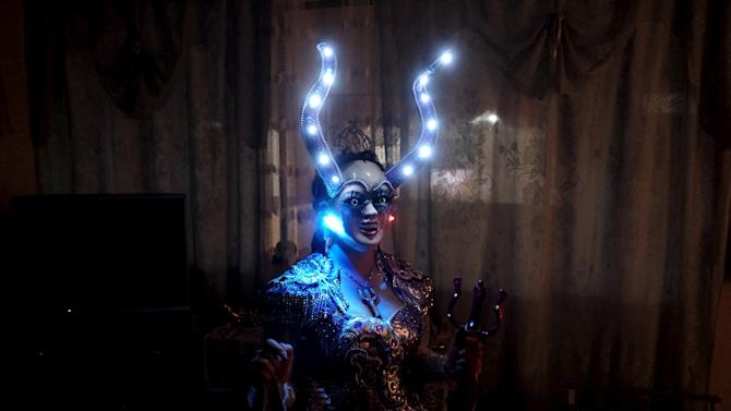 Alicia Vargas, 23, a performer from the Urus Diablada group, test the lights of her costume  ahead of a practice before Carnival in Oruro