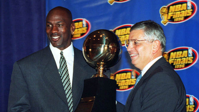 FILE - In this June 18, 1996, file photo, Chicago Bulls' Michael Jordan, left, receives the NBA Finals Most Valuable Player trophy from Commissioner David Stern during a ceremony in Chicago. Stern is not in the Hall of Fame, he never played in an All-Star game and he is about a foot shorter than most NBA stars. But try to find an NBA legacy more lasting than Stern's, who is retiring Saturday, Feb. 1, after exactly 30 years on the job. (AP Photo/Charles Bennett, File)
