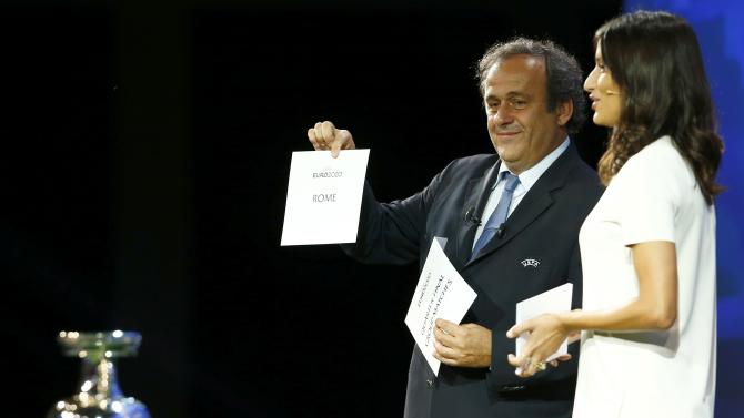 UEFA President Platini shows the name of Rome, one of the 13 cities which will host matches at the Euro 2020 tournament to be played across the continent, next to former Miss Switzerland Winiger during a ceremony in Geneva