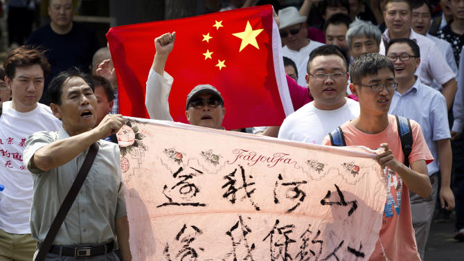 "Chinese protesters hold a national flag and a banner that reads ""Return our territory, return our people"" during a ralluy in front of the Japanese Embassy in Beijing Thursday, Aug. 16, 2012. Fourteen Chinese people were arrested Wednesday for landing without authorization on disputed islands, known as Senkaku in Japanese and Diaoyu in Chinese, in the East China Sea. The protesters had traveled by boat from Hong Kong to the uninhabited islands controlled by Japan but also claimed by China and Taiwan. (AP Photo/Andy Wong)"