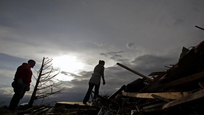 Zac and Denisha Woodcock look through the rubble of a tornado-ravaged rental home which they own Tuesday, May 21, 2013, in Moore, Okla. A huge tornado roared through the Oklahoma City suburb Monday, flattening an entire neighborhoods and destroying an elementary school with a direct blow as children and teachers huddled against winds. (AP Photo/Charlie Riedel)