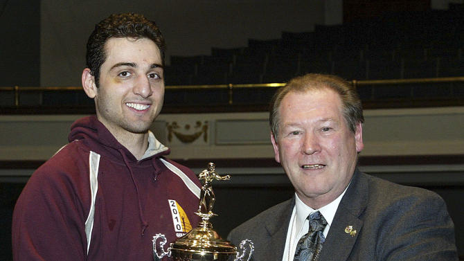 In this Feb. 17, 2010, photo, Tamerlan Tsarnaev, left, accepts the trophy for winning the 2010 New England Golden Gloves Championship from Dr. Joseph Downes, right, in Lowell, Mass. Tsarnaev, 26, who had been known to the FBI as Suspect No. 1 in the Boston Marathon Explosions and was seen in surveillance footage in a black baseball cap, was killed overnight on Friday, April 19, 2013, officials said. (AP Photo/The Lowell Sun, Julia Malakie)