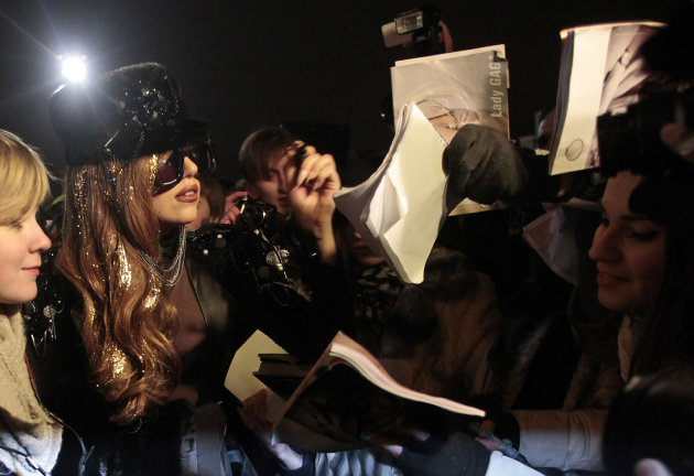 Lady Gaga, second left, signs autographs as she arrives at Vnukovo airport outside Moscow late Monday, Dec. 10, 2012. Lady Gaga, set to perform at Moscow&#39;s Olimpiisky stadium on Wednesday. (AP Photo/Pavel Golovkin)