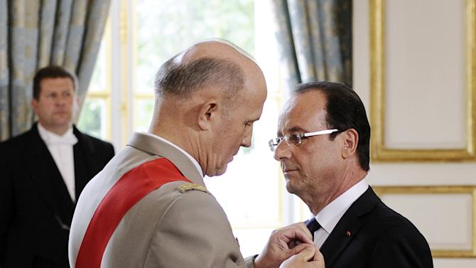 "Francois Hollande is awarded ""Grand Maitre"" in the Order of the Legion of Honor, from chancellor of France's National Order of the Legion of Honor, General Jean-Louis Georgelin, as he is officially named as France's president at the Elysee presidential Palace in Paris, Tuesday, May 15, 2012. (AP Photo/Fred Dufour, Pool)"