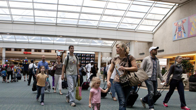 FILE - In this Friday, May 25, 2012 file photo, travelers arrive at Orlando International Airport make their way to baggage claim in Orlando, Fla. Flying this summer doesn't need to be expensive, as search engines, social media, creativity and flexibility can make finding bargain airfares easier. (AP Photo/John Raoux, File)