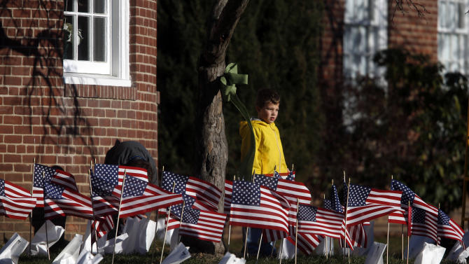 A boy stands amidst flags placed as a memorial to Sandy Hook Elementary School principal Dawn Lafferty Hochsprung, Wednesday, Dec. 19, 2012, in Woodbury, Conn.  The flags were placed in front of Mitchell Elementary School in Woodbury, Hochsprung's former school, which is across the street from the funeral home where her calling hours were held.  Hochsprung was killed when a gunman forced his way into Sandy Hook Elementary School in Newtown Friday and opened fire, killing 26 people, including 20 children. (AP Photo/Jason DeCrow)