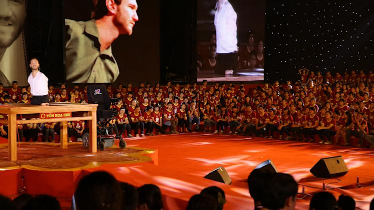 In this Thursday, May 23, 2013 photo, Nick Vujicic, a Serbian Australian evangelist who was born with no limbs, left, gives his speech to a crowd of about 25,000 students and young people at My Dinh national stadium in Hanoi, Vietnam. Vujicic's appearance is a sign of how a government that once severely restricted religion as a challenge to its authoritarian one-party rule is now taking a slightly more relaxed attitude. Those associated with Vujicic's trip said it was the first by a foreign Christian _ and the largest gathering to be addressed by a foreigner in Vietnam's recent history. (AP Photo/Na Son Nguyen)