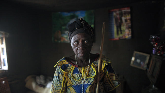 CORRECTS NUMBER OF PEOPLE KILLED TO TWO - Charlotte Ntibatekereza, who lost her son and grandson in the fighting in Kiwanja July 25 2012, stands in her house Sunday Aug. 5, 2012.  Ntibatekereza's son, his wife and her 4-year-old grandson were sleeping on the floor when a heavy-calibre bullet smashed through three walls of their home. Her son and grandson died instantly. Her daughter-in-law is in the hospital recuperating from a bullet wound to the arm in fighting last week that pitted M23 rebels against the army. The rebels have the upper hand, holding a string of eastern town as regional leaders gather Monday in Kinshasa to try to resolve a rebellion that has forced more than a quarter million people from their homes.    (AP Photo/Jerome Delay)