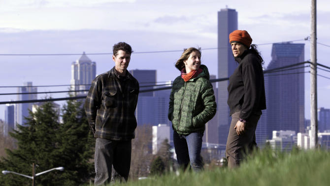 "In this March 3, 2012, photo, Glenn Herlihy, left, Briar Bates and Jackie Cramer stand on a grassy slope and talk about how they and other organizers will turn the site into a ""food forest"" in view of downtown Seattle. The park will start at 2 acres and grow to 7, offering city dwellers a chance to pick apples, plums and other crops right from the branch.    (AP Photo/Elaine Thompson)"