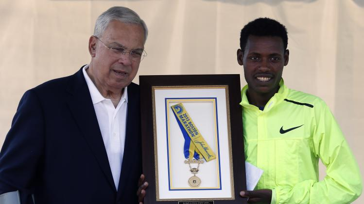 Boston Marathon 2013 men's winner Lelisa Desisa, right, of Ethiopia, holds his medal with Boston Mayor Thomas Menino after presenting it to the city as a tribute to the victims of the Boston Marathon bombings, Sunday, June 23, 2013, in Boston. (AP Photo/Michael Dwyer)