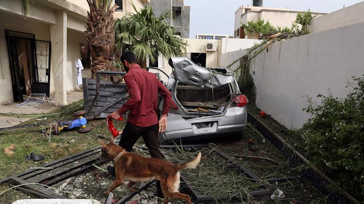 A security officer using a sniffer dog inspects the site of a car bomb that targeted the French embassy wounding two French guards and causing extensive material damage in Tripoli, Libya, Tuesday, April 23, 2013. The explosives-laden car was detonated just outside the embassy building in Tripoli's upscale al-Andalus neighborhood, officials said. (AP Photo/Abdul Majeed Forjani)