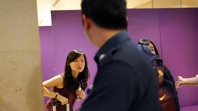 Louise Sidharta, left, from Indonesia, whose fiance was on board a missing AirAsia flight, arrives at a holding area for relatives and next-of-kin of passengers on that flight, at the Changi International Airport Sunday, Dec. 28, 2014 in Singapore. An AirAsia plane disappeared on Sunday while flying over the Java Sea after taking off from Surabaya, Indonesia for Singapore. The two countries immediately launched a search and rescue operation for Flight 8501, but there was no sign of the plane more than seven hours after it lost contact with ground control. (AP Photo/Wong Maye-E)