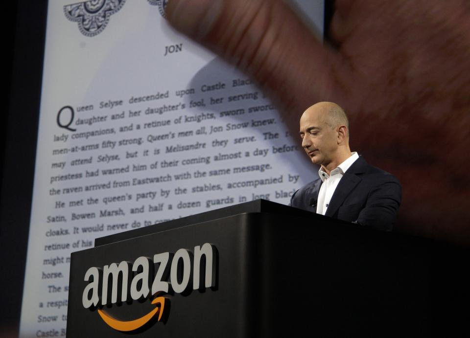 Jeff Bezos, CEO and founder of Amazon, demonstrates a Kindle paperwhite tablet at the introduction of the new Amazon Kindle Fire HD and Kindle Paperwhite in Santa Monica, Calif., Thursday, Sept. 6, 2012. (AP Photo/Reed Saxon)