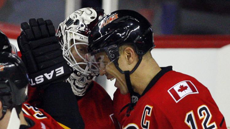 Calgary Flames' Jarome Iginla, right, celebrates with goalie Miikka Kiprusoff, from Finland, in the third period of an NHL hockey game against the St. Louis Blues in Calgary, Alberta, Sunday, March 24, 2013. The Flames won 3-2. (AP Photo/The Canadian Press, Jeff McIntosh)