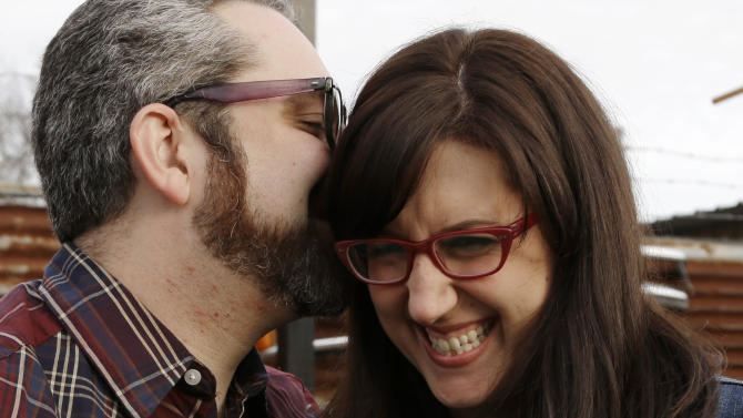 This Jan. 19, 2013 photo shows Nicole Buergers, right, and Brenden Macaluso snuggling at the eatery in Houston where they met nearly a year ago. The couple struck up a conversation about hipster eyewear over free beer and cheap eats at a Houston hangout one Sunday and have been together ever since. In this age of online dating, virtual flirting and location-based hookup by app, these two are firm believers in three-dimensional serendipity nearly a year after their first encounter.  (AP Photo/Pat Sullivan)