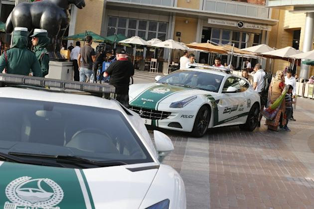 Emirati female police officers (L) stand next to Lamborghini and Ferrari police vehicles in the Gulf emirate of Dubai on April 25, 2013. Dubai police showed off a new Ferrari they will use to patrol t