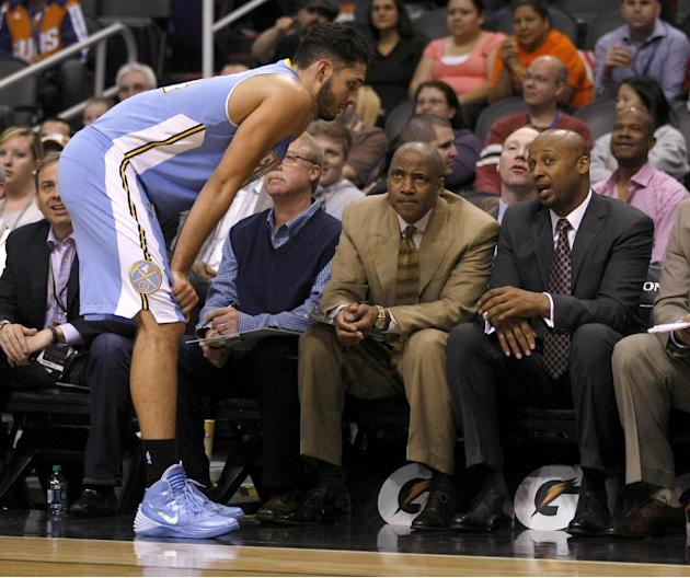 Denver Nuggets shooting guard Evan Fournier (94) talks to head coach Brian Shaw in the first quarter during an NBA basketball game against the Phoenix Suns , Sunday, Jan. 19, 2014, in Phoenix