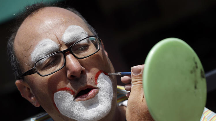 """""""Kenny the Clown,"""" otherwise known as Kenneth Kahn, applies make-up as he readies to perform in San Francisco, Friday, Aug. 17, 2012. Kahn says he unwittingly received a stolen iPad from a friend who was later arrested for breaking into former Apple CEO Steve Jobs' residence in Palo Alto. Kahn said he had the stolen iPad for a few days before police came asking for the purloined tablet, which was returned to the Jobs family. The professional entertainer said he never examined the device's contents. Instead he downloaded the """"Pink Panther"""" and other songs to play while entertaining kids and tourists during his clown routine. Kahn said had no idea where the 64GB iPad came from until his friend, 35-year-old Kariem McFarlin of Alameda, Calif., was arrested Aug. 2. (AP Photo/Marcio Jose Sanchez)"""