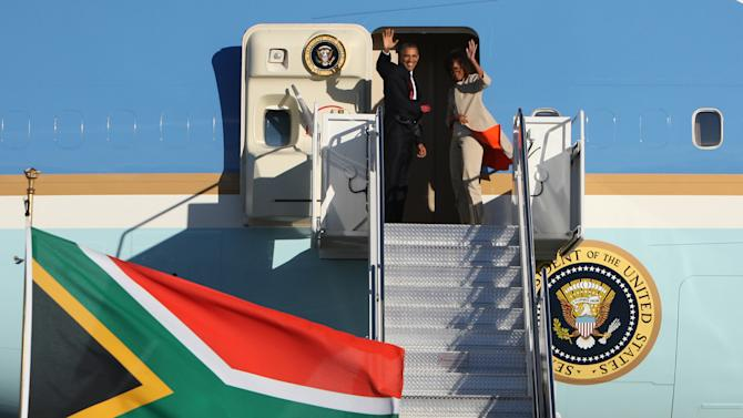US President Barack Obama, left and first lady Michelle right, wave as they board their flight on Air Force One bound for Tanzania. President Obama goes to Tanzania, kicking off the final stop on his weeklong, three-country tour of sub-Saharan Africa. (AP Photo)