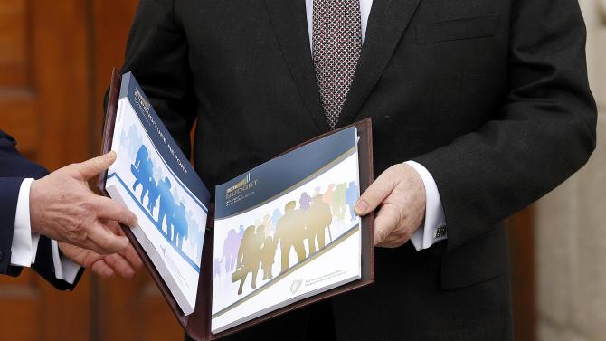 Ireland's Minister for Finance Michael Noonan displays a copy of the Budget on the steps of Government Buildings in Dublin