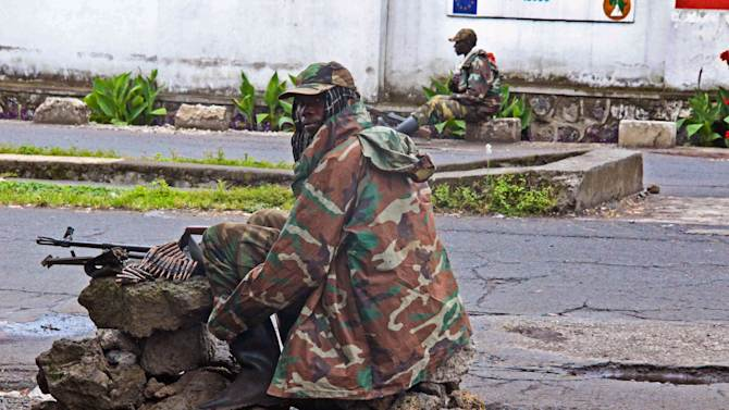 A M23 rebel soldier looks back as he and others take positions near the Heal Africa hospital in the center of  Goma, Congo, Tuesday, Nov. 20, 2012. A rebel group created just seven months ago seized the strategic provincial capital of Goma, home to more than 1 million people in eastern Congo, and its international airport on Tuesday, officials and witnesses said, raising the specter of a regional war. (AP Photo/Melanie Gouby)