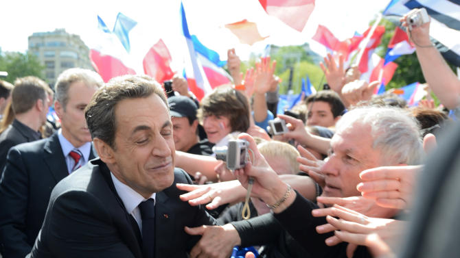 French President and conservative candidate for his re-election in the 2012 French presidential elections Nicolas Sarkozy shakes hands with supporters as he leaves a campaign rally in front the Eiffel Tower in Paris, Tuesday May 1, 2012. Polls have consistently suggested that Socialist candidate Francois Hollande will defeat Nicolas Sarkozy in Sunday's final vote, and the incumbent is trying to win over the more than 6 million voters who supported far right leader Marine Le Pen.(AP Photo/Eric Feferberg, Pool)