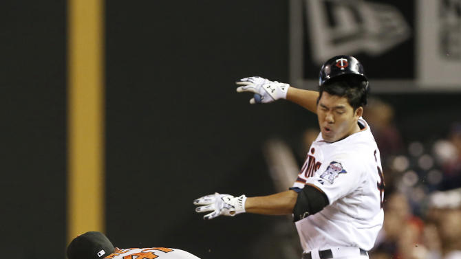 Minnesota Twins' Kurt Suzuki, right, loses his batting helmet after he was hit by the arm of Baltimore Orioles' Chris Parmelee who tried to reach the throw as Suzuki singled in the eighth inning of a baseball game, Tuesday, July 7, 2015, in Minneapolis. The Twins won 8-3. (AP Photo/Jim Mone)