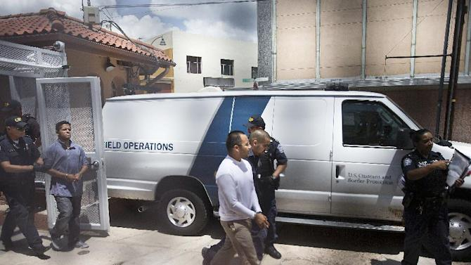 Immigration rights activists Marco Saavedra, 23, front, and Luis Leon, 20, in back, are handcuffed and led into a van by U.S. Customs and Border Protection agents in Nogales, Ariz., on Monday, July 22, 2013. They were among the eight activists from various states who asked to be allowed to re-enter the United States from Mexico on humanitarian grounds in a protest against American immigration policies. (AP Photo/The Arizona Republic, Nick Oza) MARICOPA COUNTY OUT; MAGS OUT; NO SALES