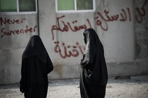 Bahraini women walk away from riot police before the start of a demonstration in solidarity with jailed political activists in the village of Diraz, west of Manama, on May 6, 2013. Bahraini security forces have arrested four people suspected of attacking a police checkpoint with petrol bombs south of Manama at the weekend, the interior ministry said