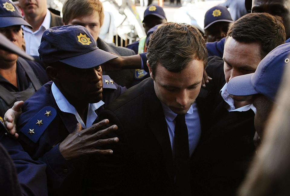 Oscar Pistorius, centre, arrives outside the magistrates court in Pretoria, South Africa, Monday, Aug. 19, 2013. Pistorius was indicted on charges of murder and illegal possession of ammunition for the shooting death of his girlfriend Reeva Steenkamp. (AP Photo)