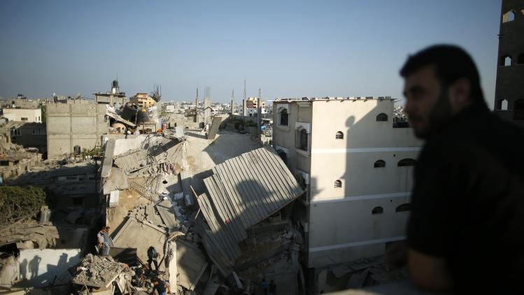 A Palestinian man stands on the roof of a building near the scene of a destroyed house in the northern Gaza Strip