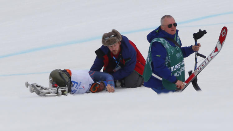 Medical staff help Tyler Walker of United States after his crash in the men's downhill, sitting skiing event at the 2014 Winter Paralympic, Saturday, March 8, 2014, in Krasnaya Polyana, Russia. (AP Photo/Dmitry Lovetsky)