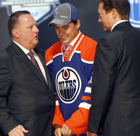 Nail Yakupov, center, a winger from Russia who was chosen first overall by the Edmonton Oilers in the first round of the NHL hockey draft, stands with Oilers officials on Friday, June 22, 2012, in Pittsburgh. (AP Photo/Keith Srakocic)