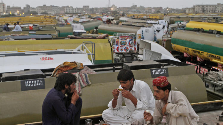 Pakistani NATO oil tanker drivers, break their fast on top of the tankers, during the Muslim holy fasting month of Ramadan, in a compound in Karachi, Pakistan, Tuesday, July 31, 2012. Pakistan and the United States signed a deal regulating the shipment of American troops supplies to and from Afghanistan, prompting Washington to agree to release over $1 billion in frozen military aid. (AP Photo/Shakil Adil)