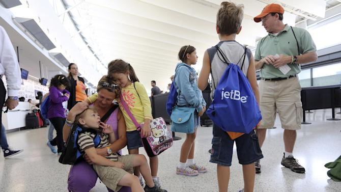 Tom Price, right, and his wife Zsuzsa, right, prepare to check in with their children, from left, Callum, 4, Keira, 6, Hailye, 10, and Owen, 9, at the JetBlue counter, Saturday, Sept. 21, 2013 at JFK airport in New York. Dozens of families with children with autism have practiced air travel at New York's Kennedy International Airport. JetBlue Airways and the nonprofit Autism Speaks held the practice run for families at JFK on Saturday. (AP Photo/Mary Altaffer)