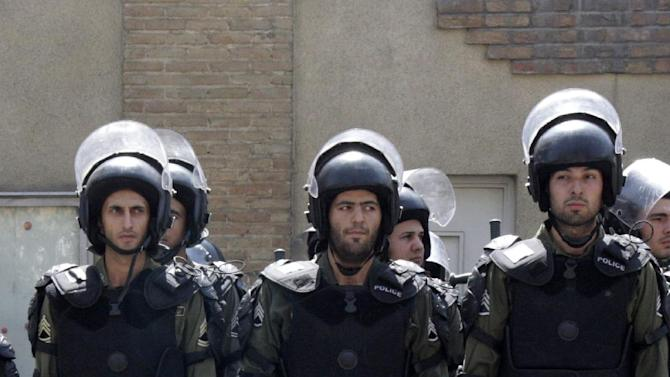 """Iranian riot police protect the French Embassy in Tehran, Iran, Thursday, Sept. 20, 2012, during a protest against the publication of caricatures of Islam's Prophet Muhammad by a French satirical weekly. Dozens of Iranian students and clerics gathered outside the embassy and chanted """"Death to France"""" and """"Down with the U.S."""" and burned the representation of the U.S. and Israeli flags Thursday. (AP Photo/Vahid Salemi)"""