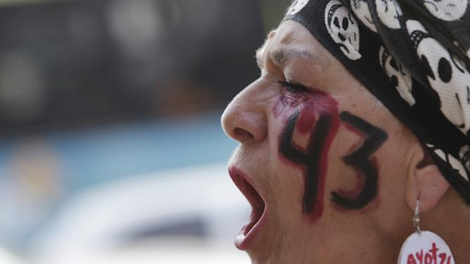 "A demonstrator with the number ""43"" painted on her face shouts as she takes part in a march to mark the 14-month anniversary of the disappearance of students from Ayotzinapa College Raul Isidro Burgos, in Mexico City"