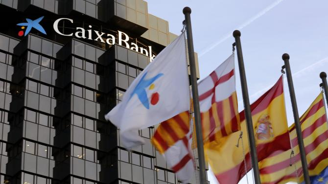 A La Caixa flag flies next to the flags of Barcelona, Spain and Catalunya in front of the bank's headquarters in central Barcelona