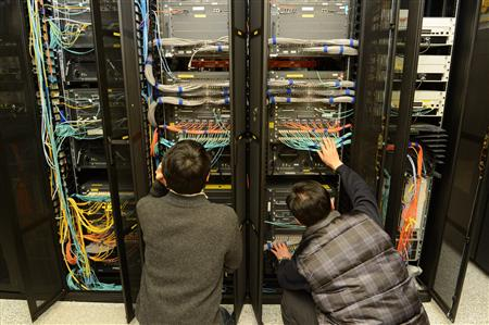 Employees of KBS inspect a server to recover it at the company's main office in Seoul
