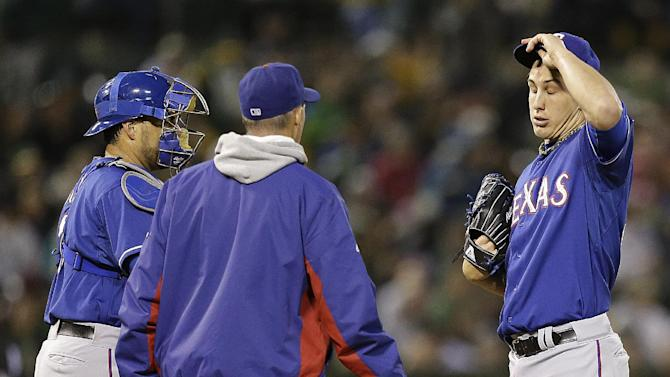 Texas Rangers' Derek Holland, right, removes his cap as pitching coach Mike Maddux, second from left, approaches the mound in the fifth inning of a baseball game against the Oakland Athletics on Tuesday, May 14, 2013, in Oakland, Calif. (AP Photo/Ben Margot)