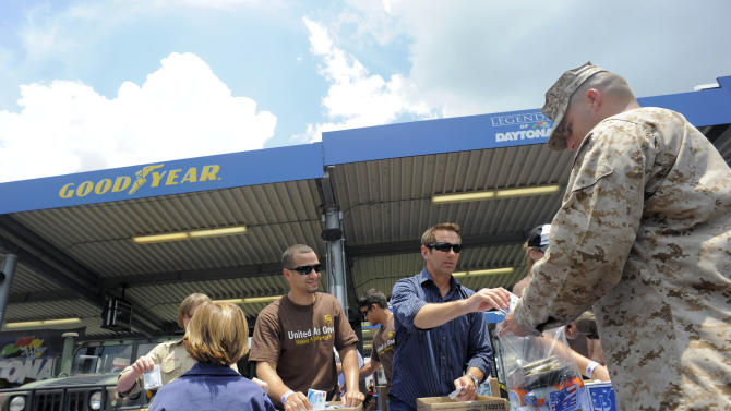 COMMERCIAL IMAGE - NASCAR Sprint Cup Series driver Greg Biffle, center, helps volunteers pack care packages for the troops at the Goodyear Gives Back  event on Thursday, July 5, 2012 in Daytona, Fla.  (Photo by Brian Blanco/Invision for Goodyear/AP Images)