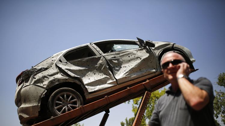 A man stands next to a car which was damaged by a rocket in the southern Israeli city of Beersheba