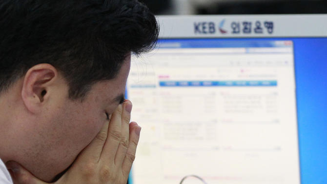 A currency trader reacts as he works at the foreign exchange dealing room of the Korea Exchange Bank headquarters in Seoul, South Korea, Friday, July 11, 2014. Asian stock markets were muted Friday, following the lead of Wall Street traders spooked by worries about the soundness of a bank in Portugal that raised the specter of more financial turmoil in Europe. South Korea's benchmark Kospi dropped 0.70 percent at 1,988.74.( AP Photo/Ahn Young-joon).