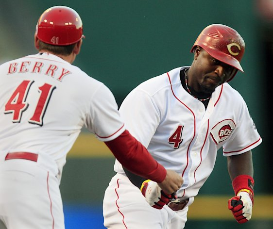 Cincinnati Reds' Brandon Phillips (4) is congratulated by third base coach Mark Berry (41) after Phillips hit a solo home run in the first inning of a baseball game against the Pittsburgh Pirates, Tuesday, Sept. 11, 2012, in Cincinnati. (AP Photo/Al Behrman)