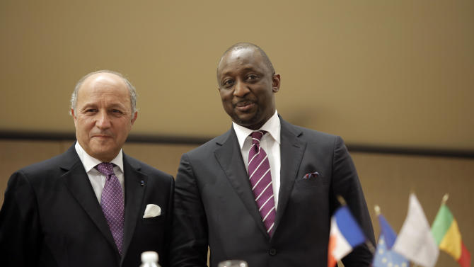 French Foreign Minister Laurent Fabius, left, and Mali's Foreign Minister Tieman Coulibaly, right, pose for journalists after a meeting in Lyon, central France, Tuesday, March 19, 2013. (AP Photo/Laurent Cipriani)